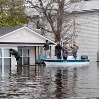 Des gens se rendent en bateau jusqu'à leur propriété, pour tenter de constater l'ampleur des dégâts.