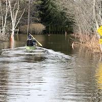 Un homme en kayak sur ce qui est, habituellement, une rue.