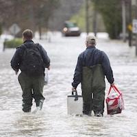 Deux hommes marchent avec des effets personnels dans une rue inondée de Rigaud.