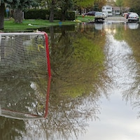 Une rue de Pierrefonds inondée, où l'on aperçoit un filet de hockey, des barrières et des voitures