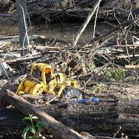 Un petit camion jaune en plastique embourbé dans la vase après les inondations