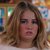 L'actrice Debby Ryan est dans un supermarché et regarde quelque chose qui la rend triste dans la série «Insatiable».