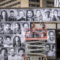 Des dizaines de photos de personnes ont été affichées sur la façade d'un édifice. Deux personnes se tiennent sur une plateforme élévatrice devant le bâtiment.