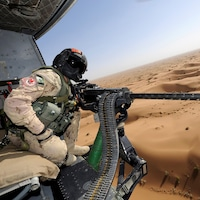Un mitrailleur installé dans un hélicoptère survolant un désert.