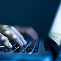 Des mains tapent au clavier d'un ordinateur portable.