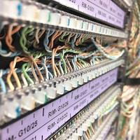 Des fils colorés branchés à des serveurs dans une salle.