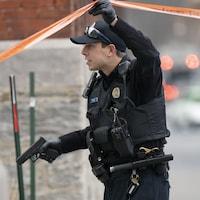 Un policier tient son arme de service à la main.