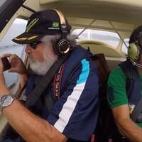 Un homme avec une barbe blanche tient un téléphone intelligent à bord d'un petit avion avec un pilote à ses côtés, en plein vol.