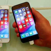 Une iPhone 7 blanc posé sur une table à côté d'un iPhone 8 noir tenu dans la main de quelqu'un.