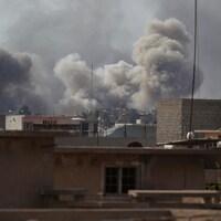 De la fumée s'élève dans le ciel, alors que les combats pour reprendre la ville de Mossoul aux mains des djihadistes du groupe armé État islamique se poursuivent.