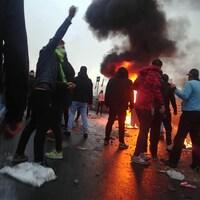 Des protestataires sont rassemblés près d'un brasier, dans la rue.