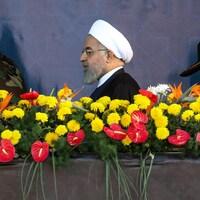 Un homme portant la barbe et un turban blanc marche derrière une haie de fleurs entre deux militaires.
