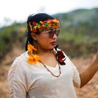 Une femme porte une couronne de fleurs et des lunettes de soleil.
