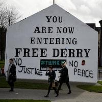 Des gens marchent devant un mur sur lequel il est écrit, en anglais, « Vous entrez maintenant dans Derry libre », avec des graffiti « No Justice » et « No Peace ».