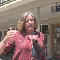 Une femme en entrevue devant un micro de Radio-Canada. La librairie Pélagie et son enseigne sont en arrière-plan.