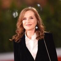 Isabelle Huppert porte une veste noire et une chemise blanche.