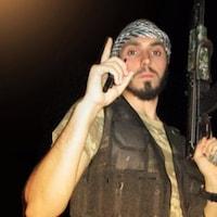 Ismaël Habib est habillé en combattant, tient un fusil d'assaut et lève le doigt en l'air pour faire le signe du groupe armé État islamique.
