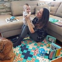 Une mère tient son bébé dans ses bras, dans son salon.