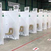 Des chaises sont séparées par des murs en cartons numérotés.