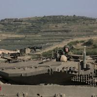 Un soldat israélien conduit un char d'assaut sur le plateau du Golan près de Majdal Shams.