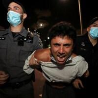 Un homme en colère est retenu par deux policiers.