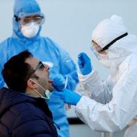 Le patient ouvre la bouche alors que le travailleur de la santé tient un coton tige.