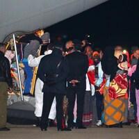 Des réfugiés sortent de la queue d'un avion cargo militaire devant le regard de policiers italiens.