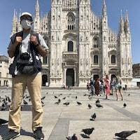 Mahmoud, caméra au cou, devant le Dôme de Milan.