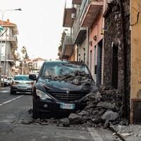 Des gravats d'un mur effondré sur une voiture garée.