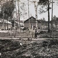 Un homme marche derrière un fil de fer barbelé dans un camp d'internement.