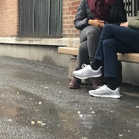 Une femme itinérante discute avec une journaliste assise sur un banc
