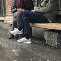 Les deux femmes sont assises sur un banc, les jambes croisées.