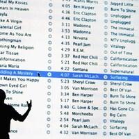 L'ombre d'un homme est visible devant un écran géant présentant une liste de nombreuses chansons disponibles sur une application.