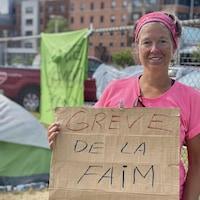 Jacinthe Comeau tient une affiche avec l'inscription «Grève de la faim», avec sa tente en arrière-plan.