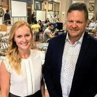 Jacqueline Cook et Brendan King se tiennent debout dans une salle de travail dans l'entreprise qui ressemble à une cafétéria.