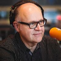 Un homme qui parle à un micro portant des lunettes et des écouteurs.