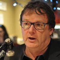 Gros plan de Jacques Létourneau, devant un microphone.