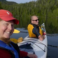 Deux kayakistes sur un plan d'eau entouré d'arbres sourient devant l'appareil photo.