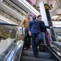 Alexandre Boulerice, Jagmeet Singh et Nima Machouf descendent les marches d'un escalier mécanique au complexe Desjardins, à Montréal.