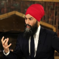 Le chef du Nouveau Parti démocratique du Canada, Jagmeet Singh en costume cravate parle avec la main levée