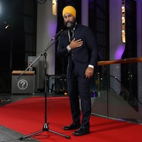 Jagmeet Singh porte la main à sa poitrine devant un micro.