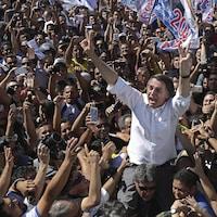 Jair Bolsonaro, candidat à la présidence du Parti national social libéral (NSBP), salue ses partisans alors qu'un membre de son équipe de sécurité le conduit, dans le quartier de Ceilandia, au Brésil, le mercredi 5 septembre 2018.