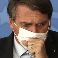 Gros plan de Jair Bolsonaro qui tousse dans son masque.