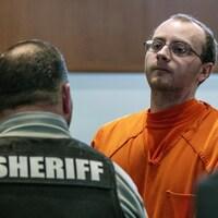 L'homme est habillé en prisonnier devant un homme qu'on voit de dos qui porte une veste de shérif.
