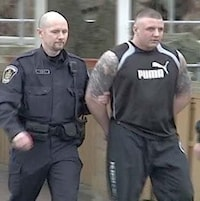 Jamie Bacon menotté est accompagné par un policier