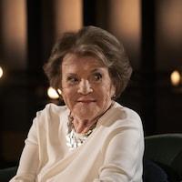 Assise, un sourire aux lèvres, Janette Bertrand regarde sur sa gauche.