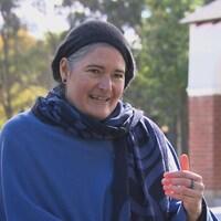 Une personne intersexuée, portant un béret noir et un chandail bleu.