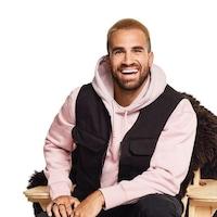 L'homme est assis sur une chaise en bois, il regarde devant lui en souriant.