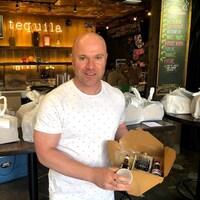Un homme chauve tient une boîte en carton avec différent type d'alcools pour préparer une margarita chez soi.