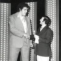 Jean Brisson serre la main d'un homme de grande taille.